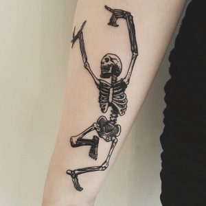 A blackwork anatomical realism tattoo of a dancing skeleton