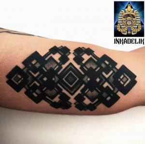 A blackwork tattoo of the endless knot symbol, representing the flow of time and movement, by Inkadelik
