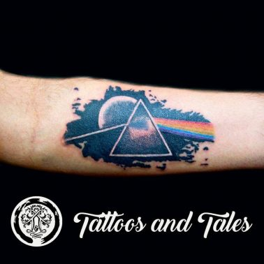 A colour and blackwork tattoo of the album art of Pink Floyd's Dark Side of the Moon by Tattoos and Tales