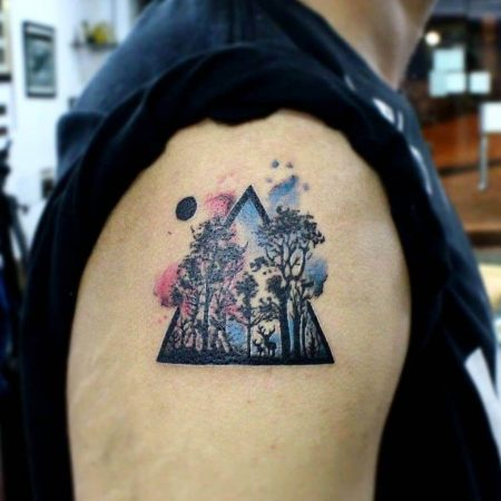 A triangle watercolour tattoo of a forest by Tattoos and Tales