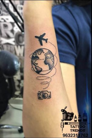 A minimalism tattoo of 'Wanderlust' featuring a plane spiraling up from a camera and going around the Earth by Tattoo Trends