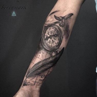 A blackwork tattoo of a compass and feathers by Birthmark Tattoo n' Customs