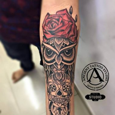 An extremely detailed abstract tattoo featuring an owl and a red rose by Ancient Tattoos