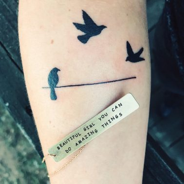 A minimalism tattoo of little black birds