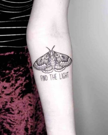 A minimalist linework tattoo of a moth with the words 'find the light' inked beneath it