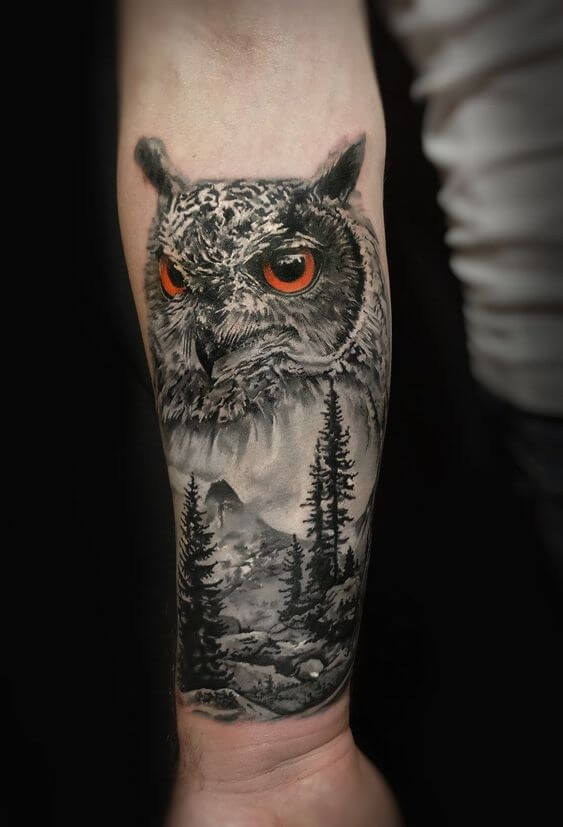 A landscape tattoo of an owl depicted using realism