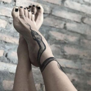 A blackwork snake tattoo around the ankle and foot