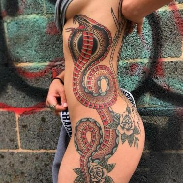 An old-school cobra tattoo stretching from the side of the ribs all the way down the thigh