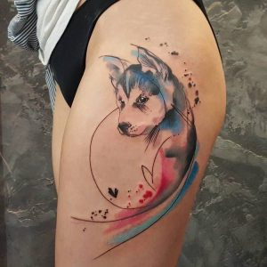 A realism tattoo of a wolf using finelining and watercolours