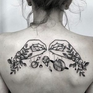 A blackwork back tattoo of two hands holding the planets on strings