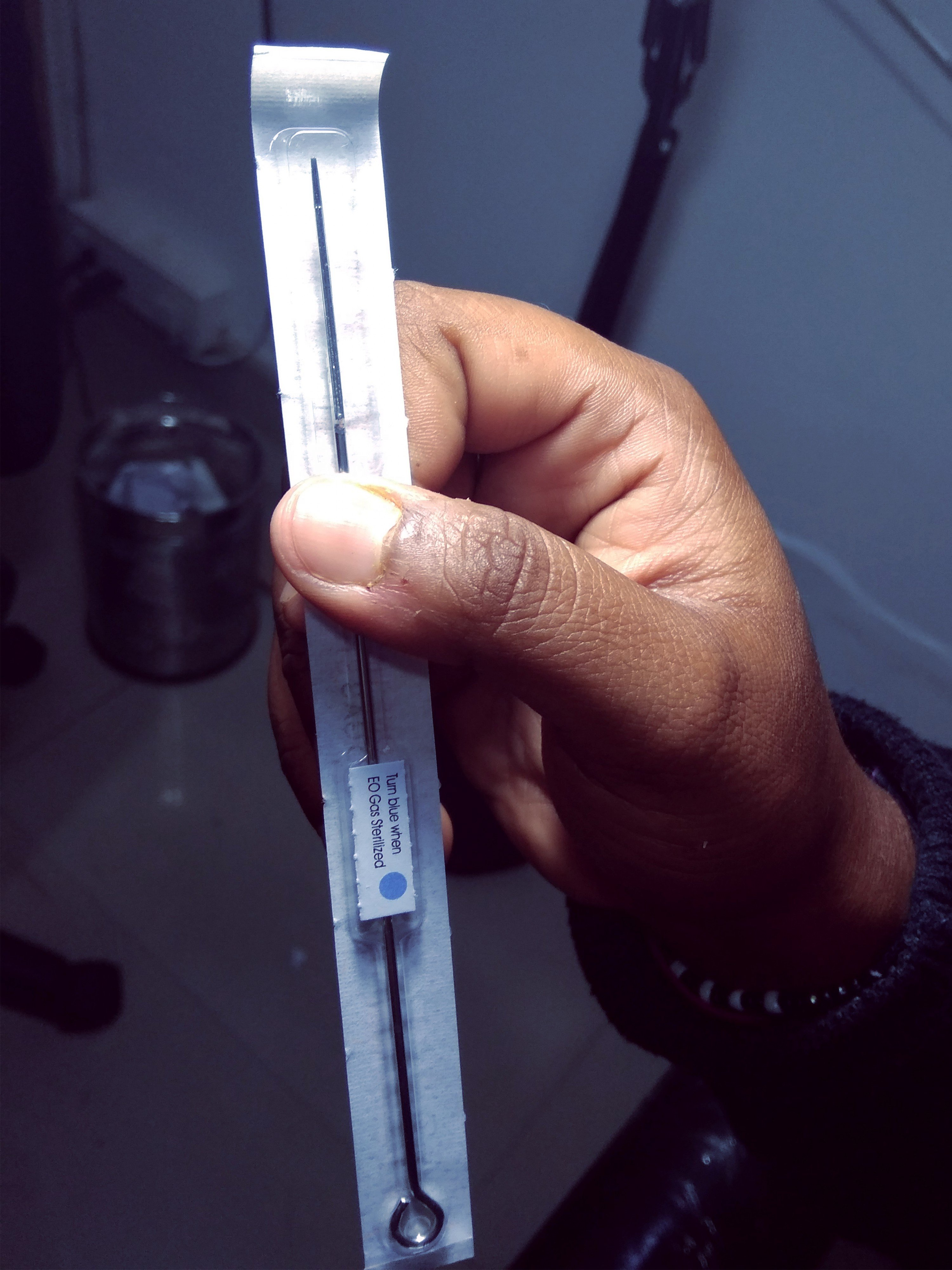 An image of Anya holding out a sealed packet with her tattoo needle inside. The packet has government-regulated labelling.