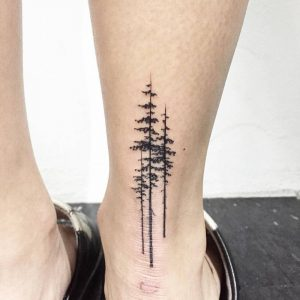 A minimalism tattoo on the back of the ankle featuring pine trees