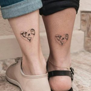 Two minimalism tattoos on the calves featuring world maps and planes in hearts