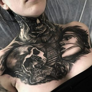 Blackwork neck and chest tattoo featuring a skull, a woman's face, and a stairway leading to a burning candle