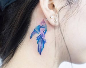 A watercolour tattoo of a fish behind the ear