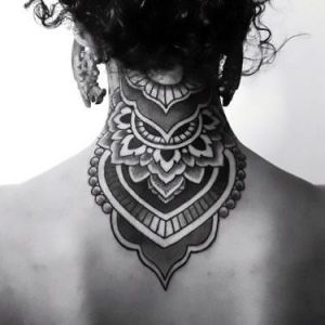 An ornamental tattoo of a filigree on the back of the neck