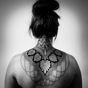 An ornamental tattoo of a mandala done on the back of the neck extending down the spine and shoulders