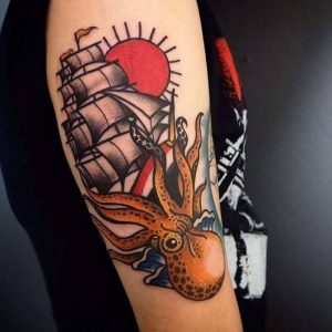 A classic old-school American tattoo of a sailing ship and an octopus
