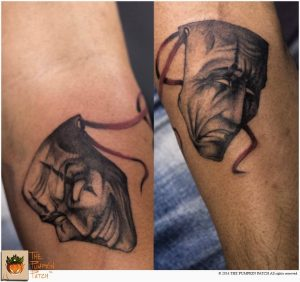 A blackwork tattoo of two masks depicting happiness and sadness, often used to represent drama, by The Pumpkin Patch