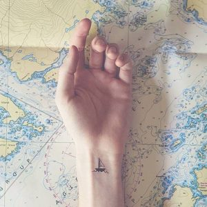 A minimalist tattoo of a boat on the wrist