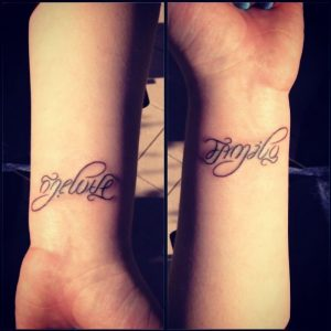 An ambigram script tattoo that says 'One Love' and when flipped says 'Family'