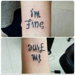 An ambigram script tattoo that says 'I'm Fine' one way and when flipped says 'Save Me'