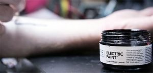 A jar of electric paint, which is the ink used to draw on a biometric tattoo