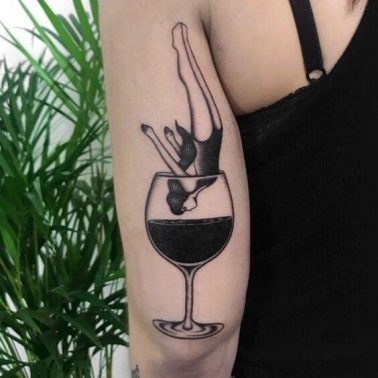 A blackwork tattoo of a glass of red wine with a woman diving into it