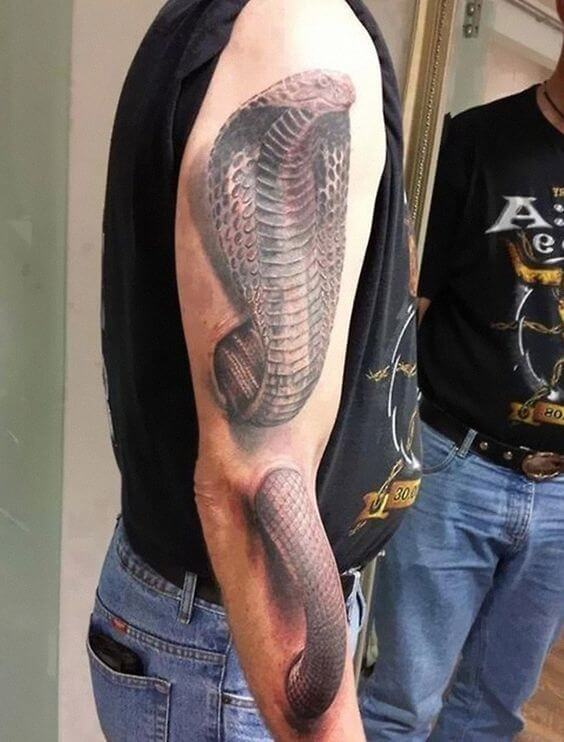 A hyperrealism 3D tattoo of a cobra going through the arm