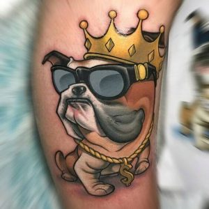 A new school tattoo of a pug wearing a crown and sunglasses
