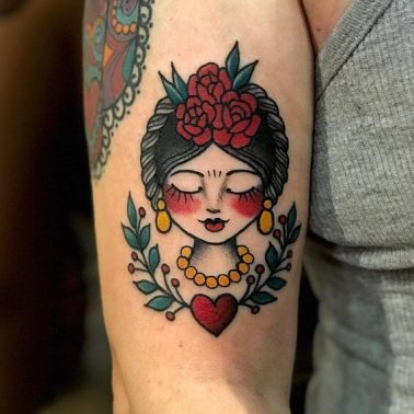 An old-school American classic tattoo of a girl in an updo wearing makeup, jewelry, and flowers