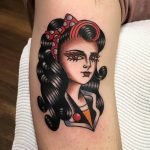 An old-school American classic tattoo of a girl sporting vintage fashion and hair