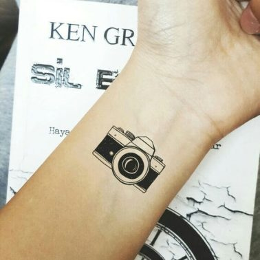 A minimalist linework tattoo of a camera on the wrist