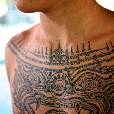 A young novice monk displays his chest tattoo of Hanuman with sak yant symbolism and script surrounding it