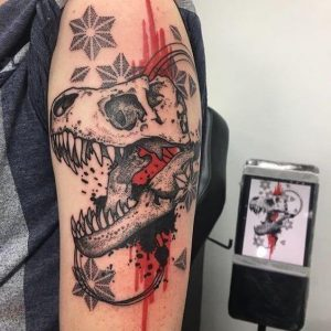 A trash polka tattoo of a dinosaur skull