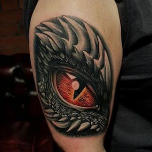 A realism tattoo of a Celtic dragon's eye on the bicep
