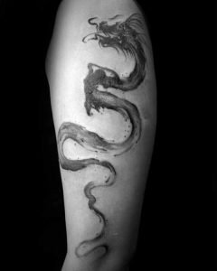 A minimalism blackwork tattoo of a serpent dragon on the bicep