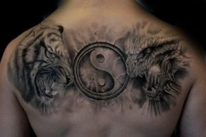 A blackwork tattoo of the battle between the tiger and the dragon using European depictions