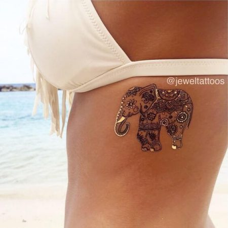 Girls rib tattoo of an elephant decorated with many small sparkly piercings