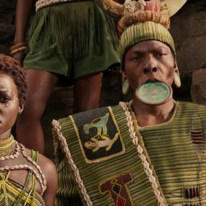A still from the Marvel film 'Black Panther' showing the water tribe's chief wearing a lip plate