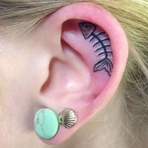 Girls ear tattoo of a fish bone with a seashell earring