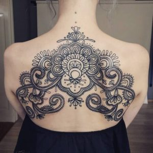 Girls ornamental back tattoo with neck piercings