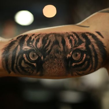 A realism blackwork tattoo of the tiger's eyes done on the bicep