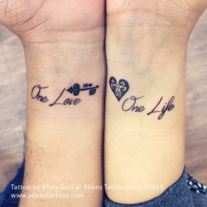 A minimalist script couple tattoo