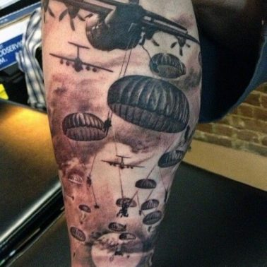 A realism tattoo of a war scene depicting jets deploying soldiers onto the field