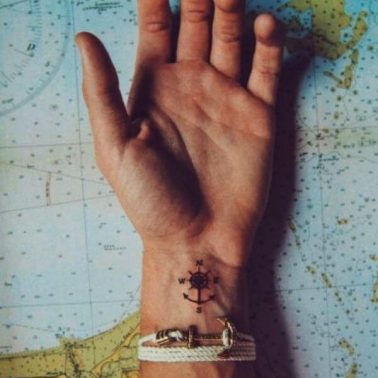 A minimalist wrist tattoo of a compass