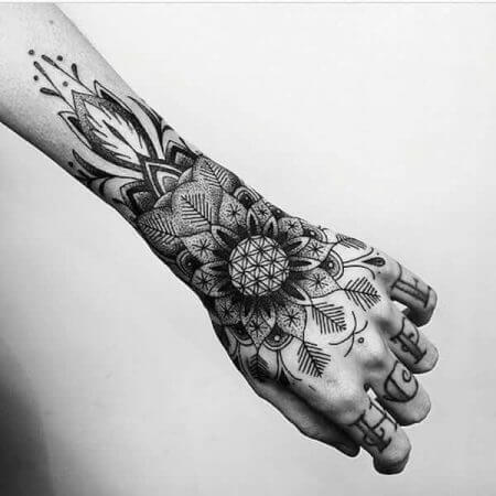 A blackwork and linework tattoo on the hand using sacred geometry and mandala patterns