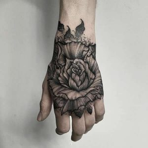 A blackwork flower tattoo on the back of the hand