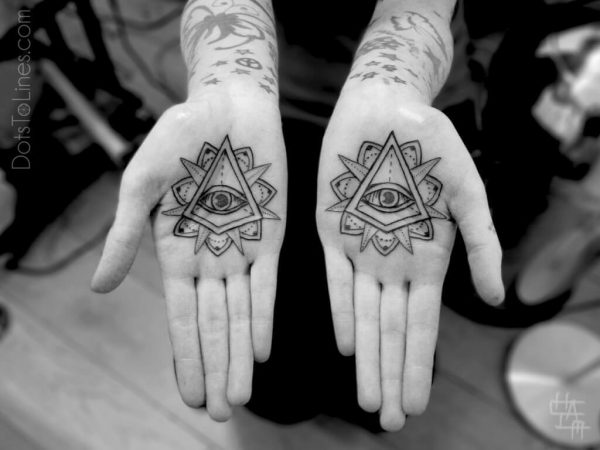 A linework tattoo of eyes within triangles on both palms