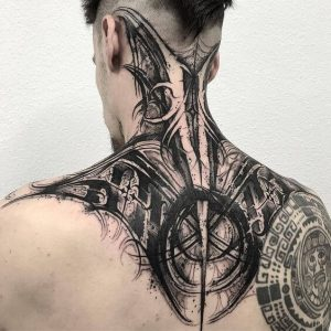 An extensive blackwork abstract neck and back tattoo